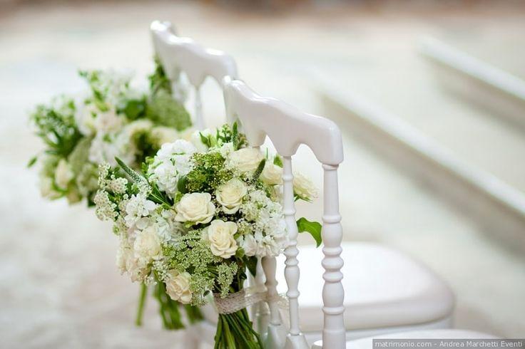 Decorazioni floreali per la sedia degli sposi. Composizioni di fiori bianchi per un matrimonio elegante