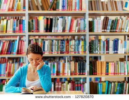 Portrait of clever student with open book reading it in college library