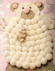 Esta alfombra además de estar elaborada conpompones de lanatiene partes tejidas. La alfombra tiene la forma de un oso, su barriguita esta hecha de pompones, mientras que la cabeza, los brazos y las patas están tejidos. Si no sabes tejer puedes optar por realizar estas partes con tela. Los