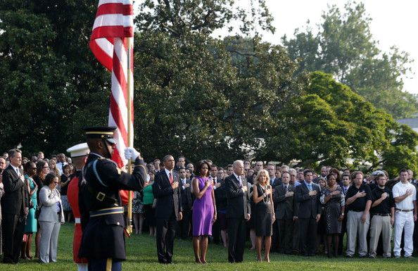 2013 ~ U.S. President Barack Obama, First Lady Michelle Obama, Vice President Joseph Biden, his wife Jill Biden, and White House staff listen to 'Taps' as they observe a moment of silence to mark the 12th anniversary of the 9/11 attacks September 11, 2013 on the South Lawn of the White House in Washington, DC. The nation is commemorating the anniversary of the 2001 attacks which resulted in the deaths of nearly 3,000 people after two hijacked planes crashed