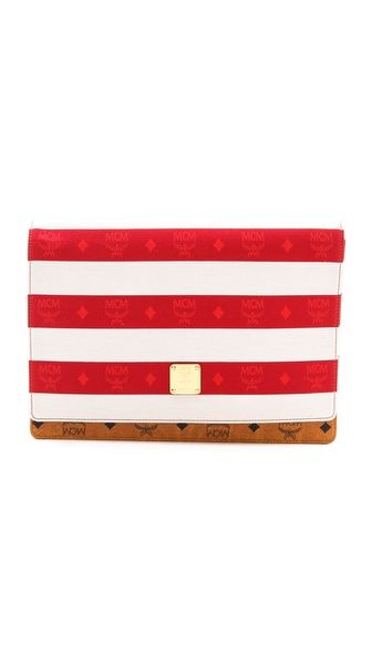 An MCM clutch created in collaboration with Phenomenon. The woven top flap is finished in a monogrammed stripe, and a gold-tone medallion adds branded appeal.