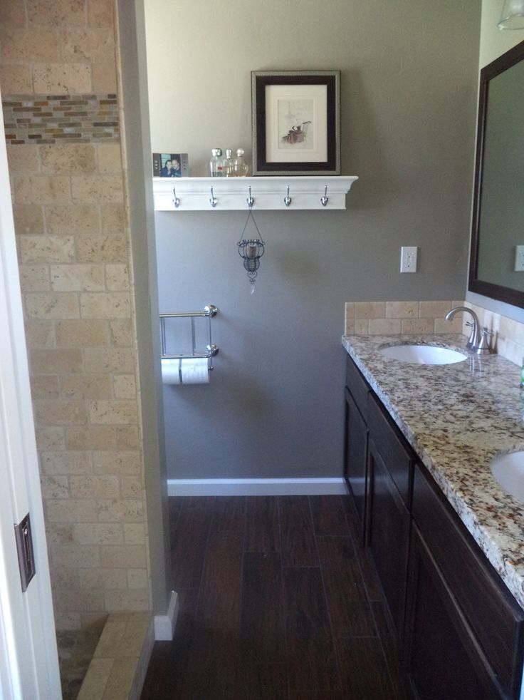 The new small master bathroom! Dark tile floors that look like wood. Refinished the cabinets to save money. New counters and new shower!