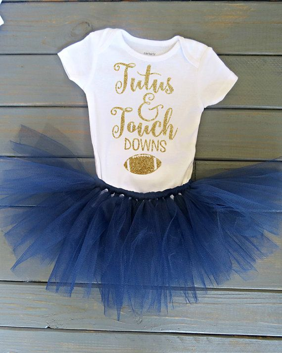 Its almost that time again and what better way to have that daddy/daughter bonding time than watching football together? This adorable tutu outfit includes a Tutus & Touchdowns bodysuit in gold glitter lettering and a navy blue tutu. (If you would like a different color tutu, send me a custom order request!) ------------------------------------------------------------------------------------------------------- Available in bodysuits size NB-18 Months and T-shirts size 2T-6. SEE PICTURES FOR…
