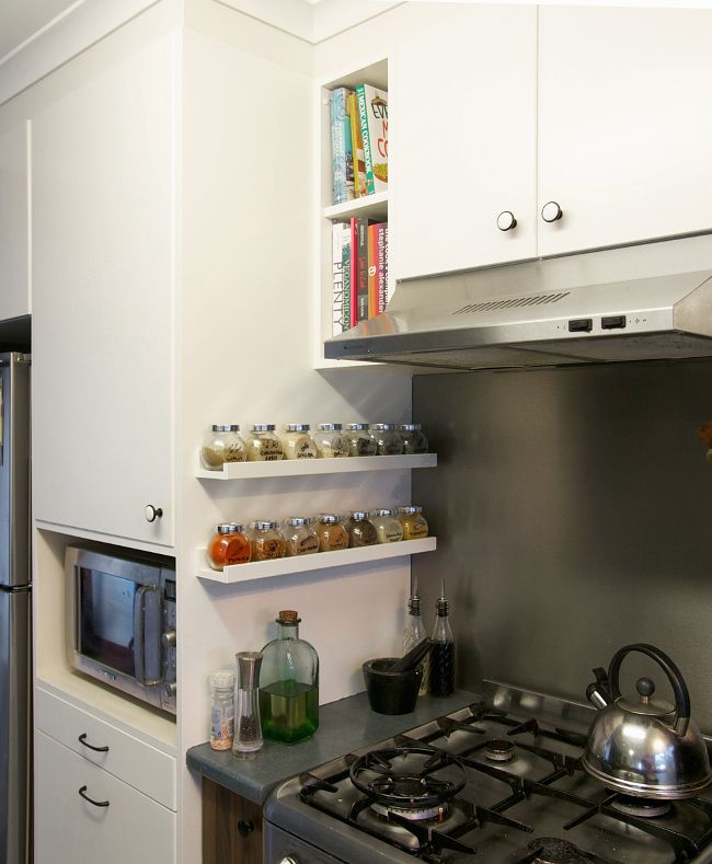 Ikea picture ledge holds spices in kitchen, like the stainless backsplash behind the stove