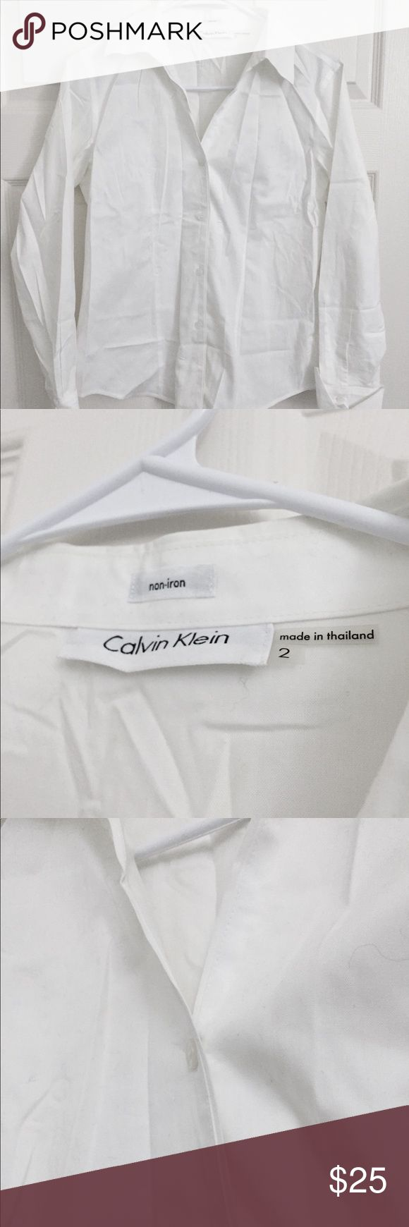 Calvin Klein white button down non iron shirt Calvin Klein white button down shirt Thick shirt material  Size 2 Non iron  (It was folded and stored in luggage bag that's why it looks crinkled..if you hang it nicely it should be easy to care)  - bundle to save Calvin Klein Tops Button Down Shirts