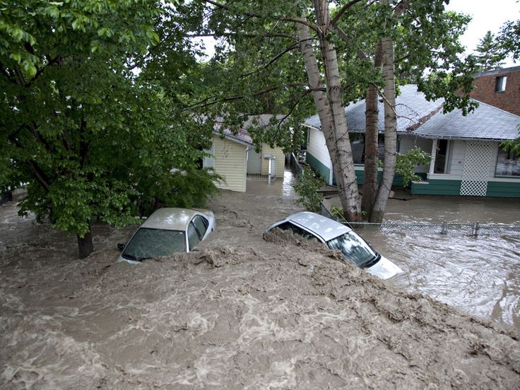 Submerged cars sits in the flood waters in High River, Alta. on June 20, 2013 after the Highwood River overflowed its banks.