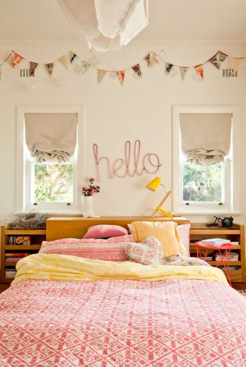 Hello!  This pink and yellow room is just too cute with its banner and soft linen shades.