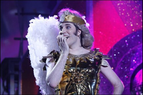 Noel Fielding, dressed as an angel, or perhaps Apollo the sun god, & looking thrilled.
