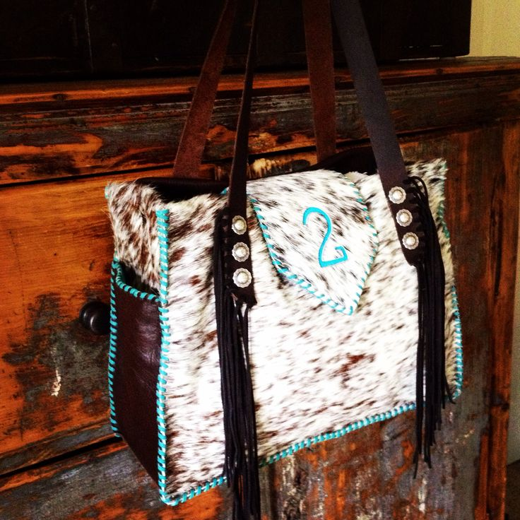A Buckaroo Diaper Tote with turquoise brand and leather back and side pickets. gowestdesigns.us