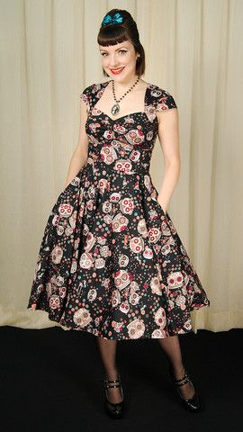 This is a perfect example of retro with an edge! This black swing dress features sugar skulls, flowers and bows all over in