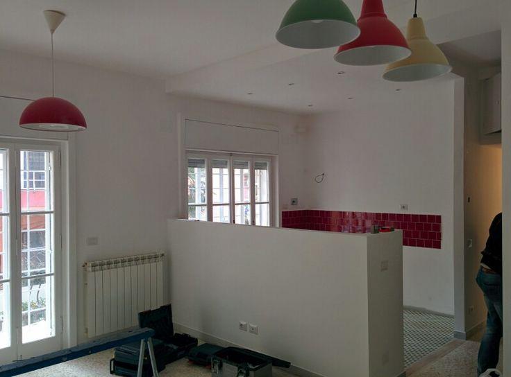 sala con angolo cottura seminascosto da muretto h130cm lampadari colorati che riprendono i colori del