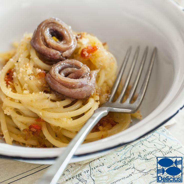 Spaghetti con crema di cipolle, acciughe e briciole
