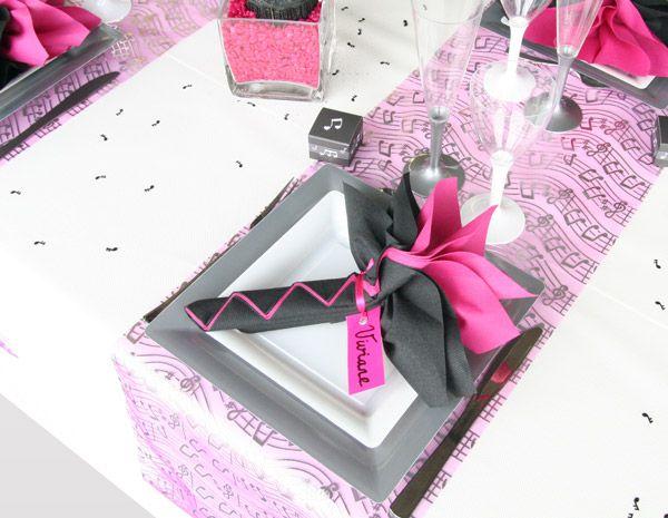 Un pliage de serviettes bicolore noir-fuchsia, auquel est attaché un marque-place satin et carton, décore le tout et le rehausse.