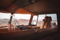 Road Trip Hipster Girl Sitting in Retro Van at beach stock photo