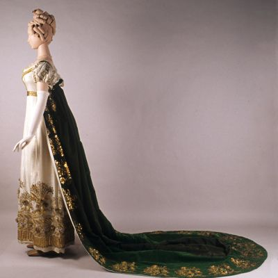 Full profile view of evening dress and court train both heavily embroidered with gold thread and decirated with pearls, ca 1815. British