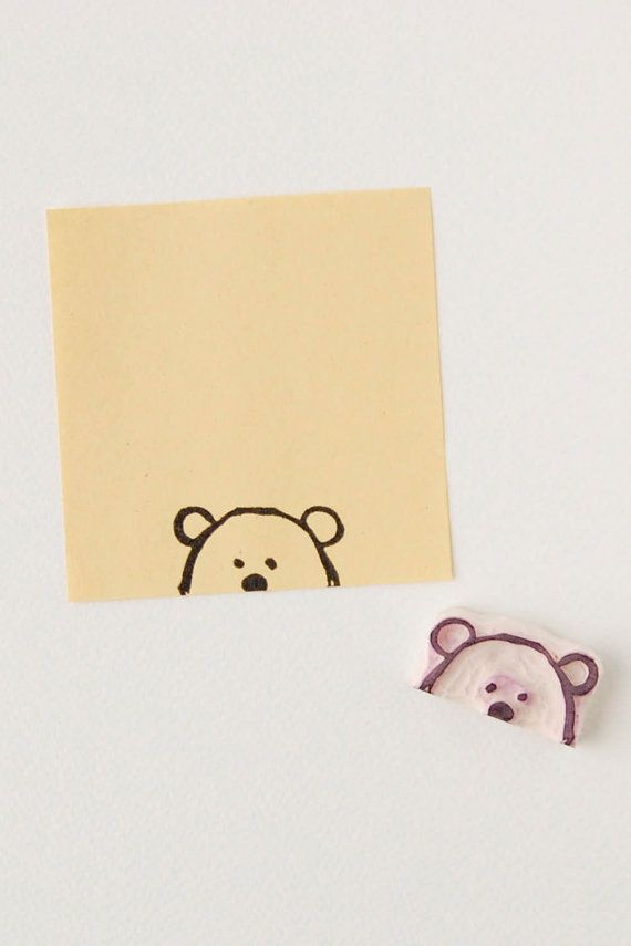 A small not mounted rubber stamp of a primitive simple bear face peering from the paper edge.  The stamp is caved from quality rubber by hand. The