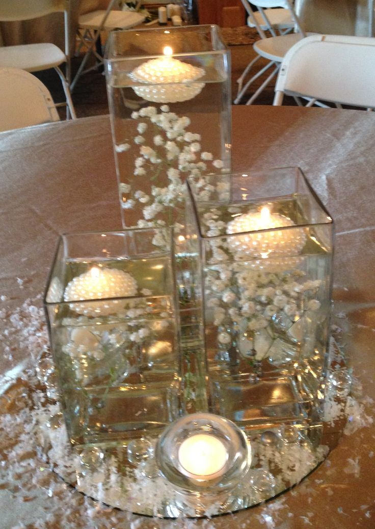 Baby's breath submerged in square vases with floating candles created for winter anniversary party.  www.fancyfloralsbynancy.com www.facebook.com/fancyfloralsbynancy