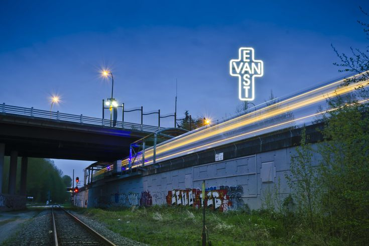 East Van sign lit up at night with the sky train passing by at VCC Clark Station.