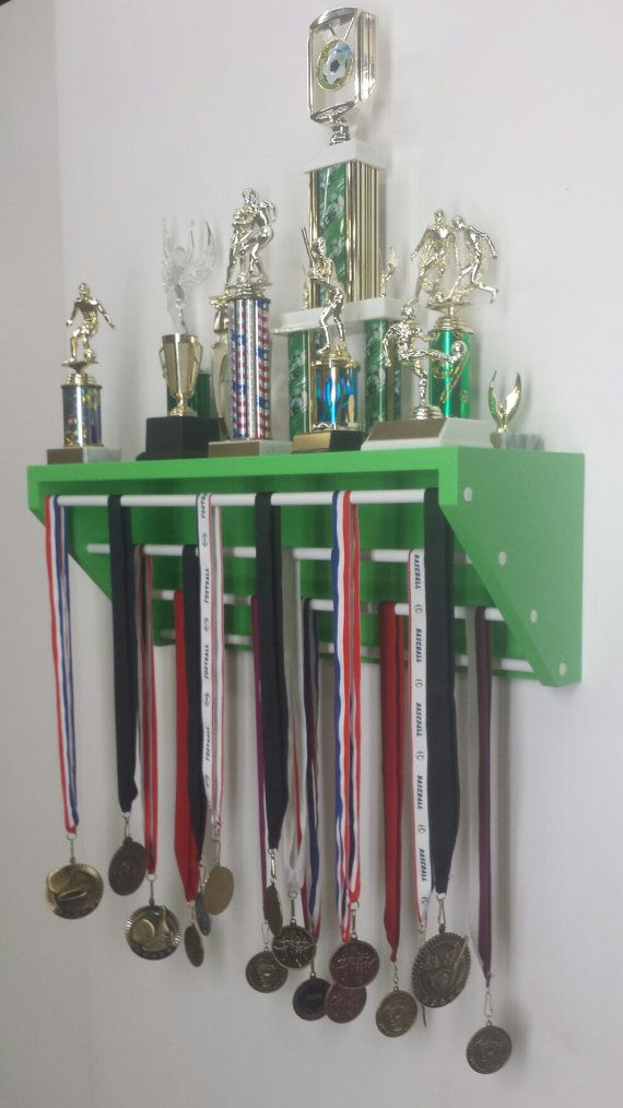 Trophy and medal display shelf (patent pending R1137542) . Choose the shelf color, then choose the rod color or colors. Four removable rods per display...mix or match the colors of your school, your team, your uniform. This item provides eight (8) feet of display space in two (2) feet of wall space. Cheerleading, gymnastics, running. Please email us if you would like more than one color of rod in the display. Choose all one color, two colors, all four rods different colors.    Shelf measures…
