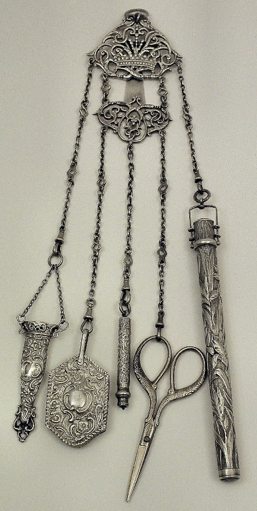 A Victorian silver four division chatelaine with embossed and scrolled ornament, Birmingham 1899, by Henry Matthews, hung with original etui (incomplete) and silver mounted ivory note pad, and now hung with Edward VII silver cylindrical bodkin case of Art Nouveau design, 6.25ins overall, London 1901, by Mordan & Co (damaged), a silvery metal propelling pencil by S. Mordan & Co, and a pair of stainless steel scissors