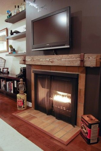 Brick around fireplace box with rustic beam as mantle. Rich paint color and floating shelves are a nice touch as well. I love this simple yet elegant...my style