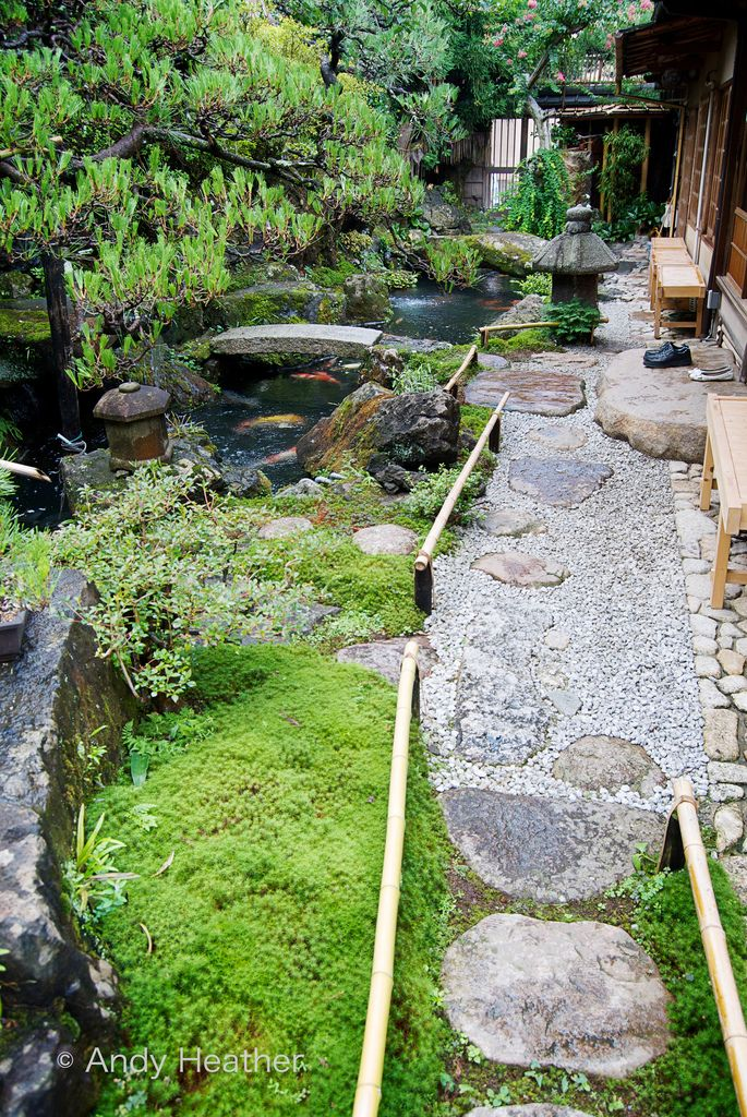 Two customers have entered a Japanese townhouse cafe and left their shoes on the door stone. To the left is a pond full of prize winning koi carp. A pebble and cobblestone path leads from the cafe through the garden past a stone lantern towards the sliding door at the end of the garden that leads to Kyoto's Nene no Michi.