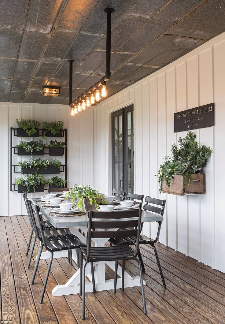 Wood beams cover the floors and walls of the porch, whose black and white schemeand black metal chairs and plant boxes and recycled tin roof  give it an industrial feel, but also a farmhouse vibe