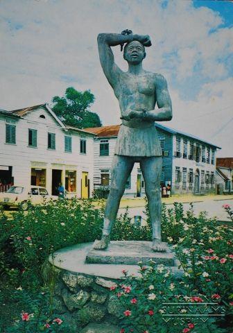 Het standbeeld Kwakoe, ter herdenking van het  einde van de slavernij, staat op de hoek Zwartenhovenbrugstraat / Sophie Redmondstraat. Het is gemaakt door Joseph Klas. Ook als prentbriefkaart uitgegeven, in uitgave van F.Ch. SJIEM FAT, domineestraat 27, Paramaribo.  Datum: Locatie: Paramaribo, Suriname Vervaardiger: Ed Hogenboom Inv. Nr.: 26-13 Fotoarchief Stichting Surinaams Museum