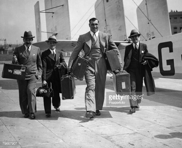 Boxing, London, England, 21st May, 1932, Italian heavyweight champion boxer Primo Carnera carrying his suitcases as he arrives at Croydon aiport with his entourage for his upcoming fight (Photo by Popperfoto/Getty Images)