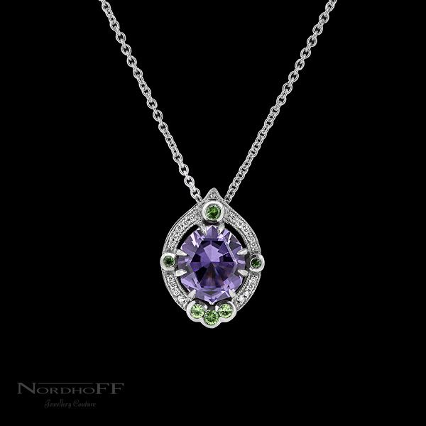 This custom made white gold pendant features a lively precision cut purple Amethyst from Arizona, accented by bright white diamonds and delicious green Tsavorite garnets.