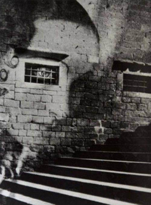 Con un ojo brillante, cuidaba los pasos de los transeúntes para que todos tropezaran. Un movimiento involuntario para sacudir la polilla de la realidad. - Staircase to the Cathedral, España (1937) - Kati Horna