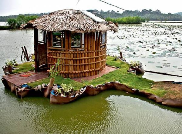 Small floating Island with green cottage rests on 5,000 used plastic bottles