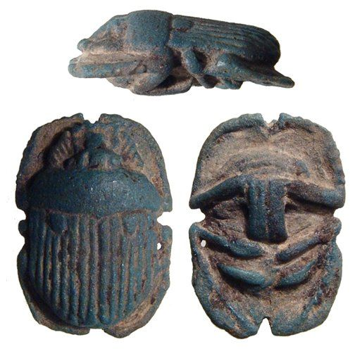 Egyptian scarab button scarab, Late Period, 664-30 B.C. Blue faience, naturalistically rendered with striated wing case and loop on bottom for attachment to the bandages of a mummy, 3 cm long. Private collection