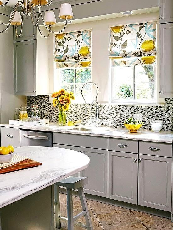 Don't be afraid to add some pattern and textures to your kitchen design. If you already have chosen a color scheme in the space, think about using a fabric to create window shades that play into your already existing color choices. In this kitchen, the fabric on the Roman shades contains a gray that is similar to the paint used on the cabinets and other accents were used to play off the yellow floral design in the fabric.