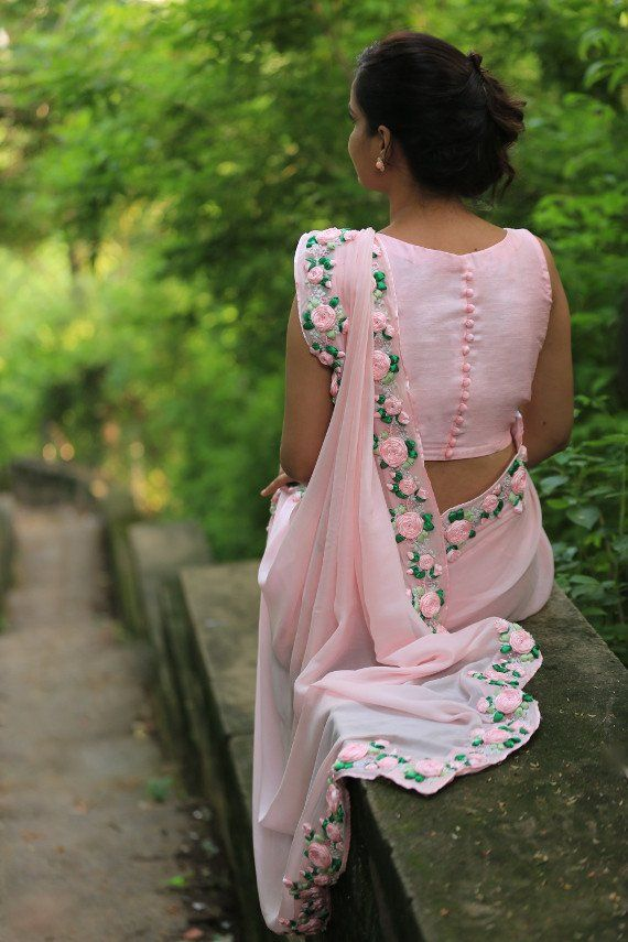 PRODUCT DESCRIPTION: Featuring a balmy baby pink pure chiffon saree with beautifully embroidered satin pink rose vines along the edges. It is embellished with French knots and glistening pink pearls. It comes with an unstitched raw silk blouse piece with baby pink rose buds and an unstitched matching satin petticoat fabric. NOTES: Colours may appear slightly different due to photography lighting conditions and your monitor display settings. SHIPPING/DELIVERY: This product will be shipped…