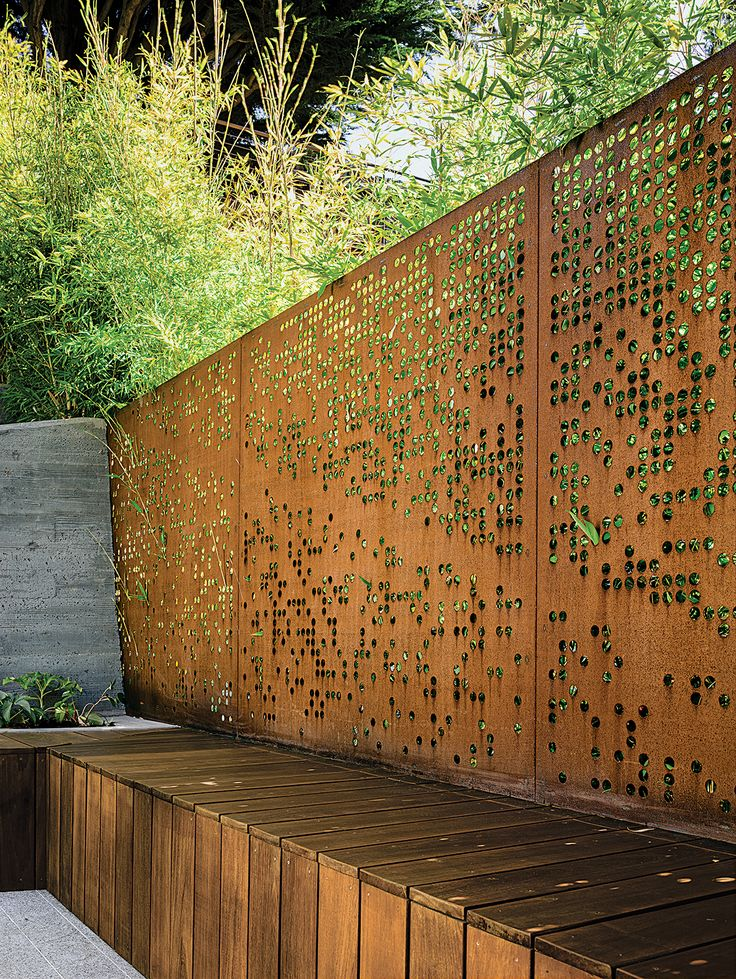 With input from her clients, Barensfeld used a computer to generate the circular patterns that were carved into a pair of Cor-Ten steel screens with a water-jet cutter. The perforations allow light and the green of the surrounding Koi bamboo to filter into the space while preserving privacy.