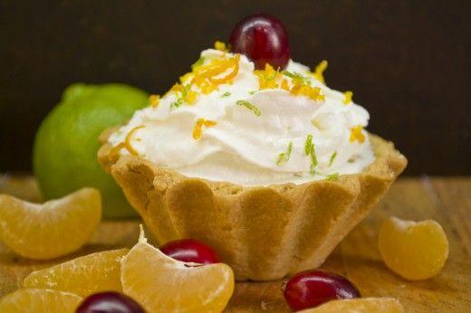 Тарталетки с апельсиновым курдом с лаймом и мандаринами  Простой, но очень красивый и вкусный праздничный десерт. Тарталетки из нежного и рассыпчатого песочного теста, заполнены нежнейшим и ароматным апельсиновым курдом. Украсить пирожные можно взбитыми сливками, свежими ягодами, кусочками фруктов, или приготовить для украшения итальянскую меренгу и посыпать крем цукатами.