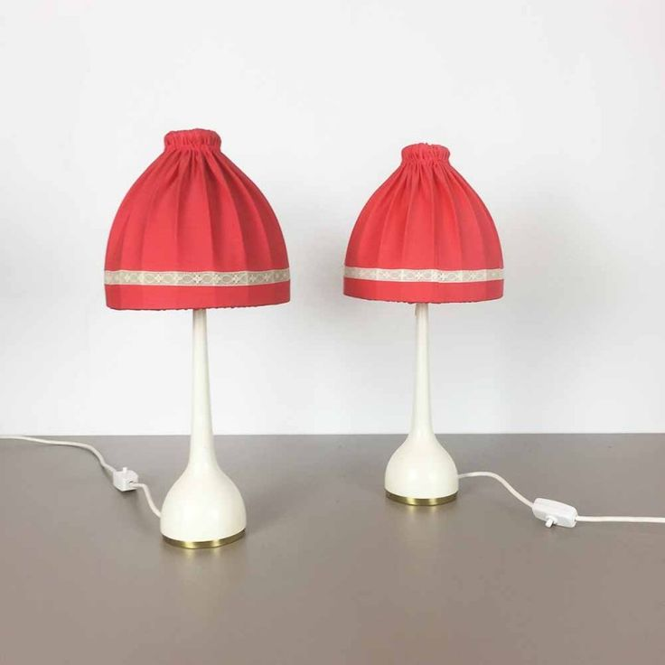 <p>These table lamps are designed by Hans Agne Jakobsson in the 1960s and manufactured by HAJ AB in Markaryd, Sweden. It comprises a white lacquerd base with original fabric shades. one of the shades is a bit lighter than the other. each lamp is 50cm high and has a diameter of 22cm. The lights are in a good vintage condition, slight traces of use. one of the base has some little scratches.</p>