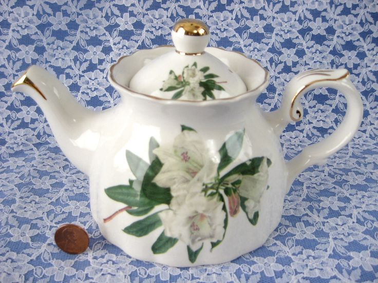 This is a Royal Patrician, England bone china teapot made in a pattern of white Rhododendron or Azalea blossoms and leaves. The teapot measures 4.75 inches high by 8 inches long and holds 2-3 cups or