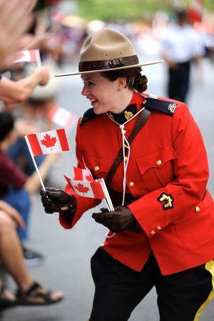 Canada Day Parade Photos: Montréal Edition: Royal Canadian Mounted Police woman, handing out Canadian Flags during the Montréal Canada Day Parade. 2016