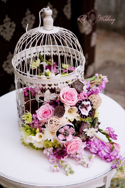 Wedding Flowers in white bird cage.. kinda has a rustic feel to it