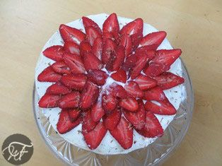 A classic baked cheesecake with a sour cream top and fresh strawberries