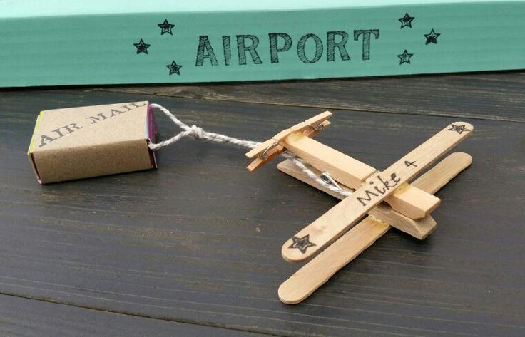 """Houten diy vliegtuigjes met daaraan een doosje rozijntjes.. De doosjes zijn voorzien van een wikkel met de tekst """"air mail"""""""