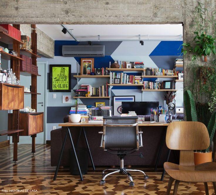 Escritório integrado com sala de estar. Parede com pintura geométrica em cinza e azul.