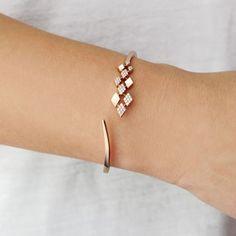 Staggered diamond and yellow gold diamond-shaped cuff bracelet.