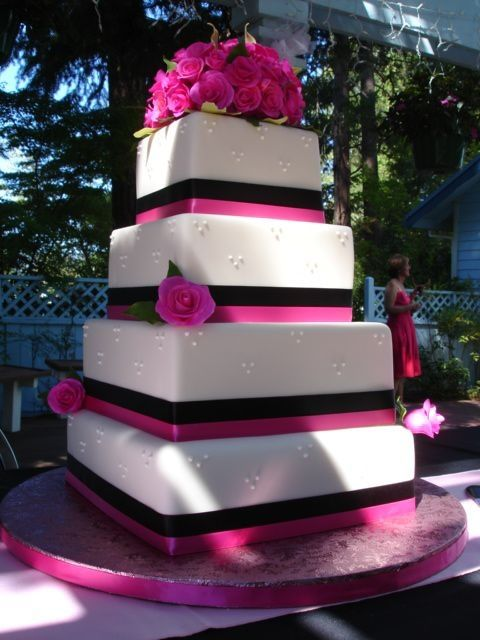 This is not my cake, just a cake I like. 4 tierd cake with hot pink GP roses and black and hot pink ribbon.  I had to deliver this cake 361 miles it did beautifully.  Not a broken rose of leaf.  I added the bottom tier when I got to Oregon.  Had to decorate it in a hotel room.  TFL