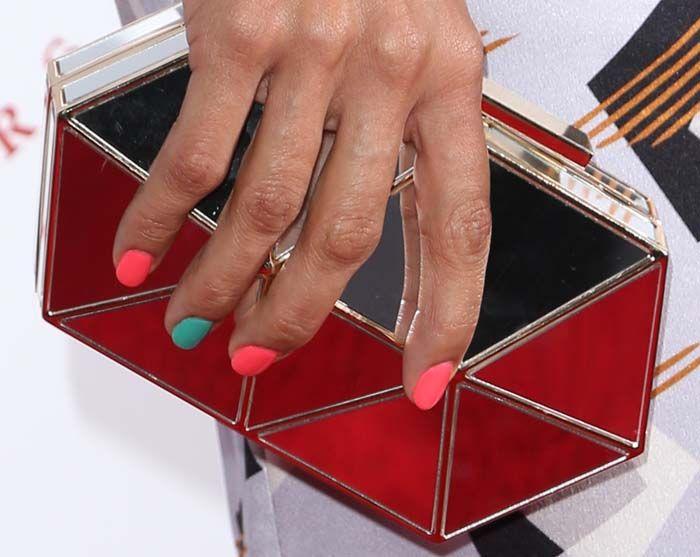 Rosario Dawson holding a geometric metallic 'Aleni' clutch from Vince Camuto