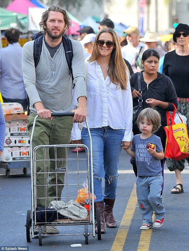 Family day out: The actress walked beside husband Christopher Jarecki and held their littl...