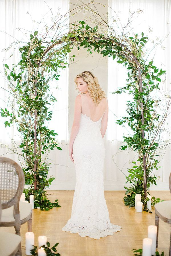 An arboreal ceremonial arch featured flowering white cherry branches and camellia foliage. | Photo by Deborah Zoe