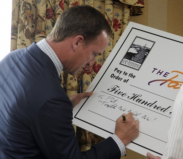 Denver Broncos quarterback and former Vol Peyton Manning signs a check from himself and his wife Ashley Manning for $500,000 to UT coach emeritus Pat Summitt and her son Tyler Summitt for The Pat Summitt Foundation at the Cherokee Country Club, Thursday, April 11, 2013. The foundation was formed to help in the research and fight against alzheimer's disease. (AMY SMOTHERMAN BURGESS/NEWS SENTINEL)